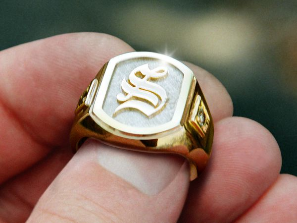 Custom signet ring cast and fabricated of yellow and white gold with birthstone accents